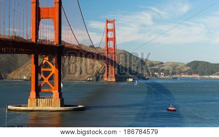A pilot boat awaits a large cargo ship to enter the bay under the Golden Gate Bridge in San Francisco at dusk