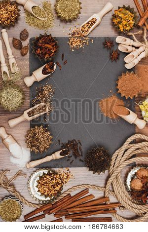 Different spices in bakeware with wooden scoops on the slate slone background top view
