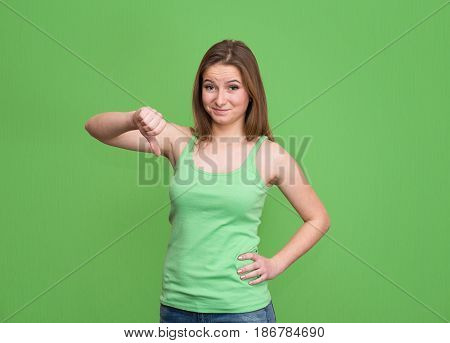 Negative human face expressions emotions feelings attitude life perception body language. Unhappy angry displeased teenage girl giving thumb down hand gesture isolated on green background.