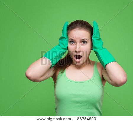 Tired frustrated and shocked cleaning woman screaming. Stressed spring cleaning woman in green rubber gloves looking at camera. Isolated on green background