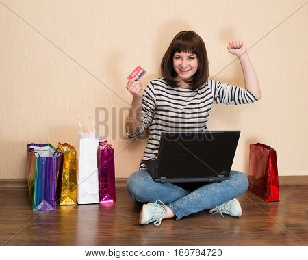 Happy girl with shopping bags sitting on the floor with laptop and credit card shopping online. Young woman shopping online at home.
