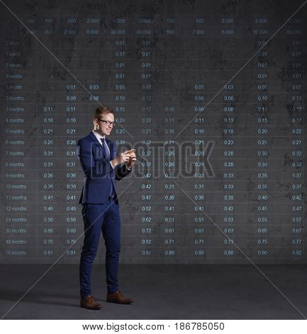Businessman with smartphone standing on a diagram background. Business, office, investment concept.