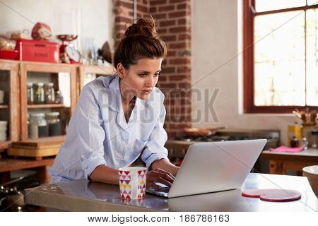 Young woman in pyjamas using laptop in kitchen, close up