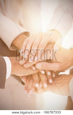 Close up of business team stacking hands on white background