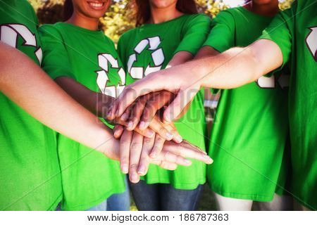 Midsection of volunteers stacking hands while standing at park