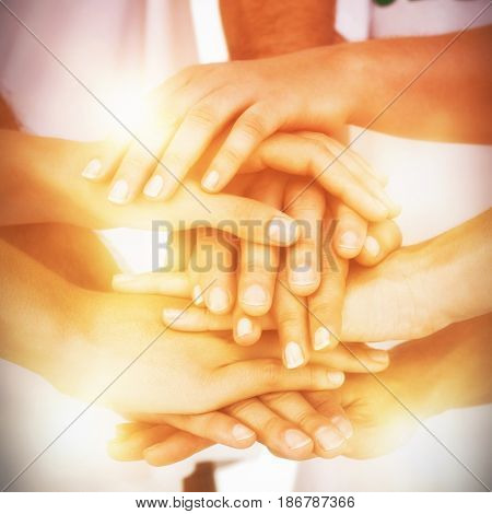 Mid section of volunteers putting hands together on white background