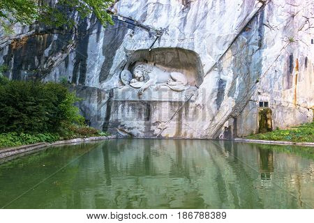 Luzern Switzerland - April 30 2017: Luzern dying lion monument on the stone cliff with the pond in the foreground in Luzern Switzerland.