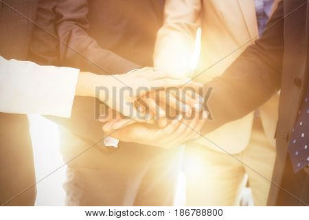 Midsection of business people stacking hands while standing in office