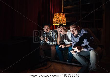 Three young guys addicted to video game. Psychological disorder, problems of excessive play, addiction, unhealthy lifestyle concept