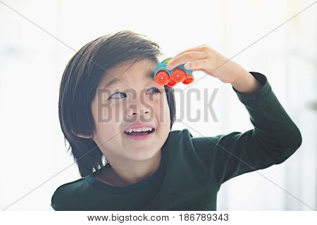 Cute asian child playing toy cars in the room