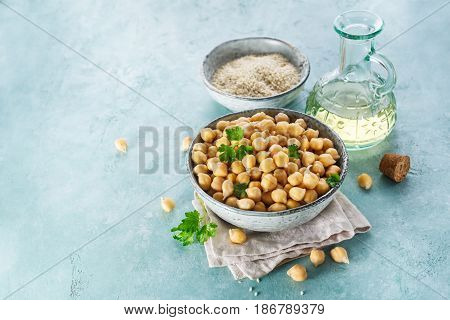 Ingredients for cooking hummus. Chickpeas sesame seeds and oil. Food background with copy space for your text.