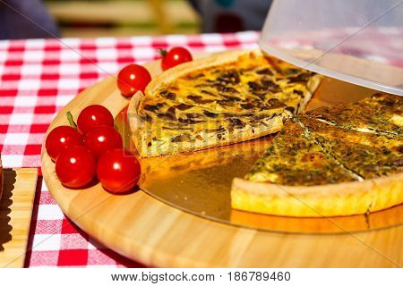 Pieces of closed pie with herbs lying on a table with cherry tomatoes