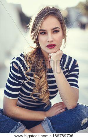 Blonde Woman, Model Of Fashion, Sitting In Urban Background.