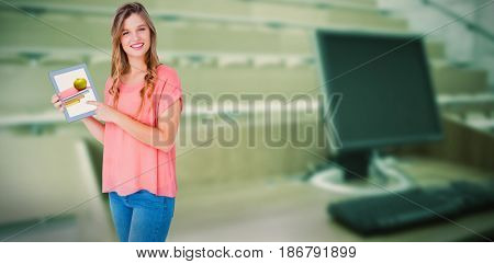 Hipster woman showing tablet pc against computer monitor with empty seats in a lecture hall