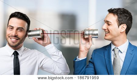 Men talking on tin can phone