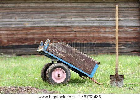 Old retro garden wheelbarrow and shovel on the lawn next to the house / garden trucking