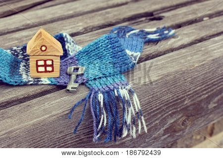 Small house with a key in scarf on wooden surface / warming technologies for life