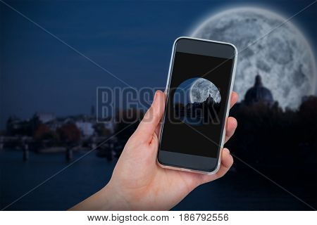 Hand holding mobile phone against white background against large moon over river city
