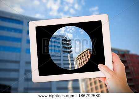 Masculine hand holding tablet against modern buildings against sky