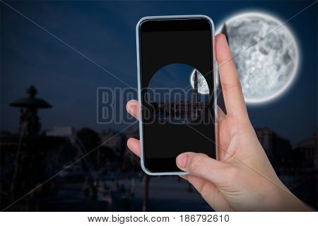 Human hand holding mobile phone against white background against large moon over city