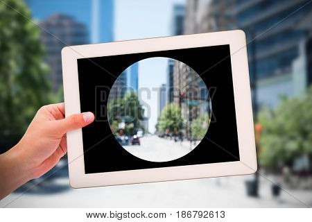 Masculine hand holding tablet against blur view of a modern city