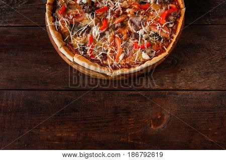 Italian traditional food background. Appetizing delicious pizza served on wooden rustic table, flat lay. Dark background with free space for text.
