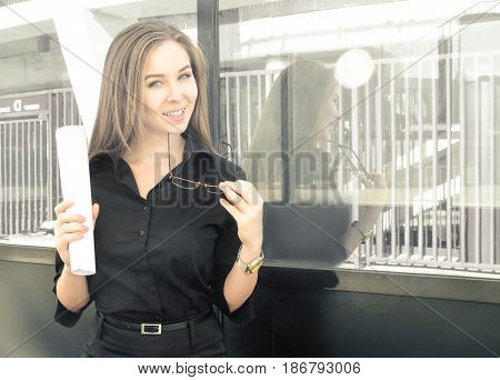 Photo of an attractive businesswoman who laughs standing near the building with papers and glasses in her hands. In a black shirt hair is weaved looks at the camera