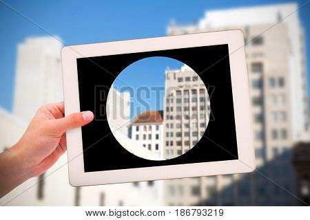Masculine hand holding tablet against building structures against blue clear sky