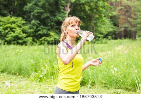 Portrait of surprised fit young woman drinking water after her exercise