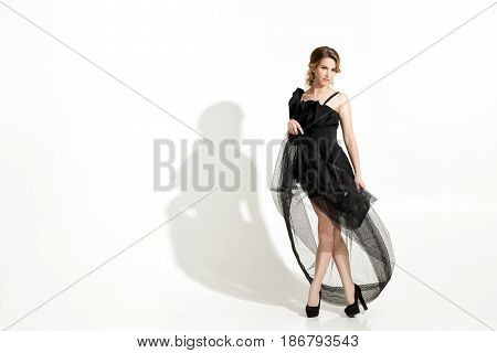 fashion shot of elegant and sexy young woman in a black dress and veil on white background