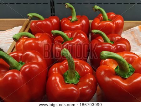 Red sweet pepper in a wooden box. Box with red peppers in the food store. Fresh vegetables, organic food.