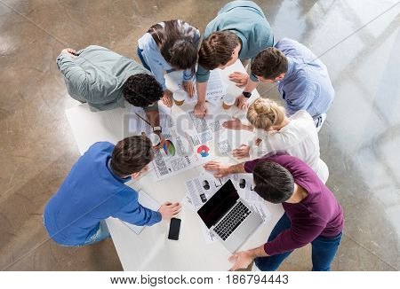 Overhead View Of Professional Businesspeople Discussing And Brainstorming Together On Workplace In O