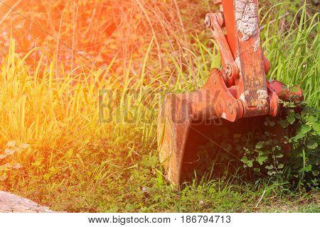 bucket small excavator orange crawler bulldozer in working with sunrise light