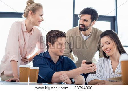 Group Of Young Business People Using Smartphone On Small Business Meeting