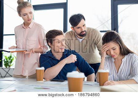 Group Of Young Business People Looking At Colleague On Small Business Meeting