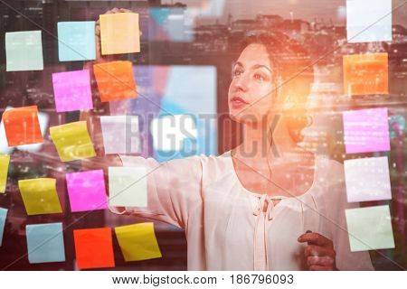 Illuminated cityscape against businesswoman sticking adhesive notes on glass