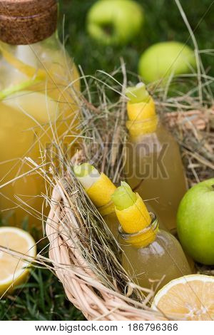 Refreshing lemonade with apple and lemon in a picnic basket. Cold summer drinks in garden