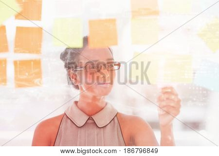 Illuminated cityscape against young designer holding sticky notes on glass