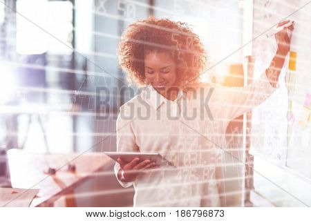 Stocks and shares against businesswoman writing on whiteboard while using digital tablet