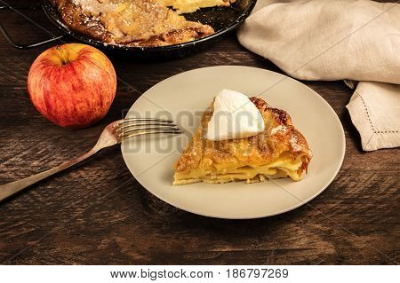 A closeup photo of a piece of a homemade apple pie with a scoop of ice cream, with the rest of the pie in a skillet in the blurred background, with a place for text