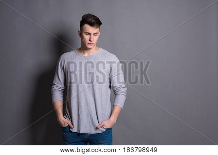Young macho man portrait at studio grey background. Portrait of a confident stylish guy. Boy style, trendy hipster with cool hairstyle