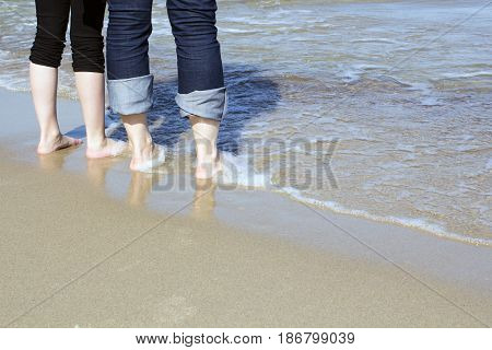 Couple at the Beach with feet in the bright summer sunlight
