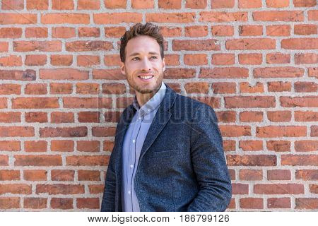 Man professional businessman portrait. Smart casual urban business man smiling happy at office building or city street. Handsome man wearing suit jacket indoors.