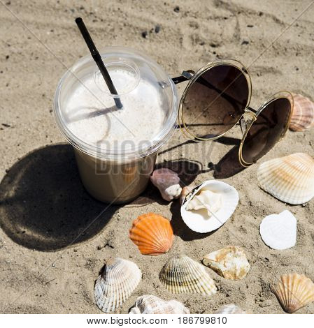 Ice latte on sand with cockleshells and glasses