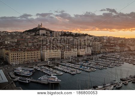 View of the Vieux Port and Notre Dame de la Garde in Marseille at sunset