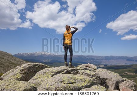 Back Woman Looking Into Distance From Rock Top Of Mountain
