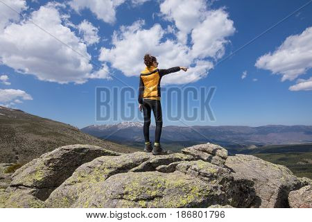 Back Woman On Top Of Mountain Pointing With Hand