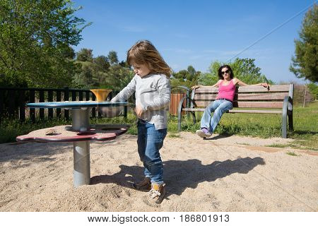 Child Playing And Mother In Bench Watching