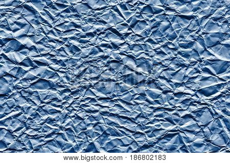 the old crumpled sheet of paper of blue color for the abstract textured background and for wallpaper