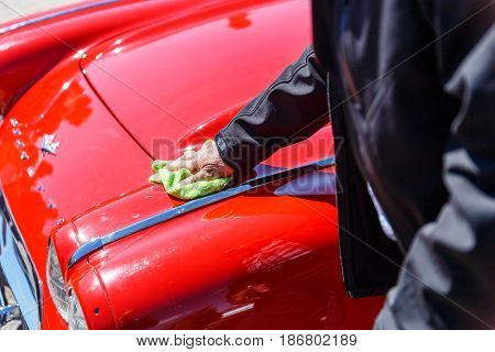 A man wipes a hood with an old or retro car